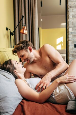 cheerful and shirtless man laughing with woman in bedroom