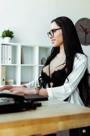 Selective focus of smiling sexy secretary using computer at table