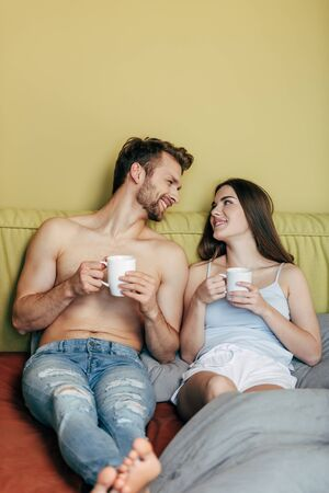 selective focus of happy couple looking at each other and holding cups with coffee