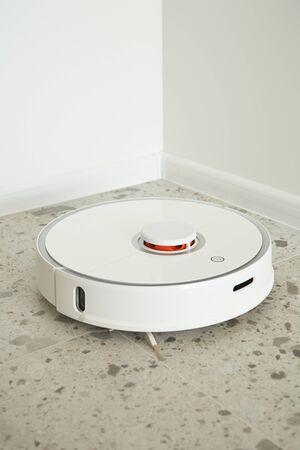 modern robotic vacuum cleaner washing floor tiles near white walls