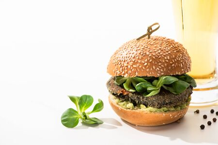 delicious green vegan burger with microgreens, oil, black pepper on white background