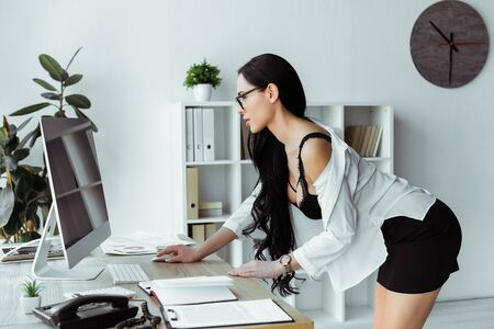 Side view of seductive secretary using computer near papers in office