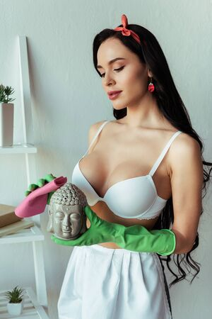 Sexy woman in bra and apron cleaning decorative statuette with rag at home Standard-Bild