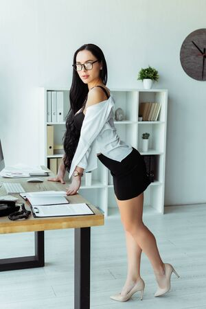 Side view of seductive secretary in bra looking at camera near working table