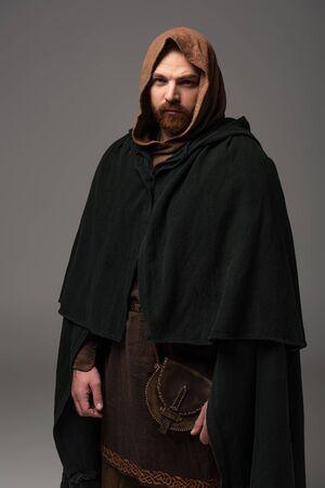 serious medieval Scottish redhead man in mantel on grey background Zdjęcie Seryjne