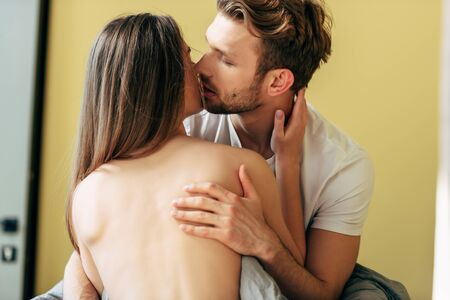seductive and naked woman hugging and kissing with boyfriend in bedroom Standard-Bild