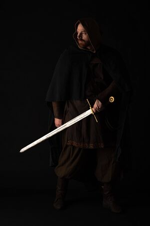 medieval Scottish man in mantel with sword in dark isolated on black