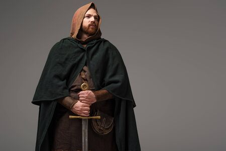 medieval Scottish redhead knight in mantel with sword on grey background Zdjęcie Seryjne