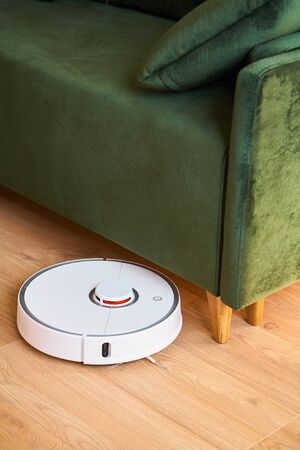 modern automatic vacuum cleaner washing floor near green sofa in living room