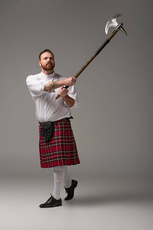 Scottish redhead man in red kilt raising battle axe on grey background