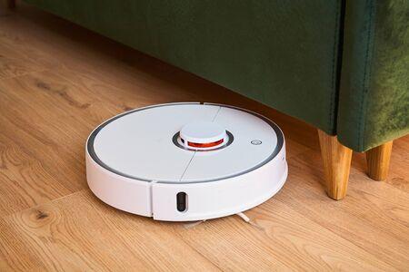 robotic vacuum cleaner washing floor near green sofa 版權商用圖片