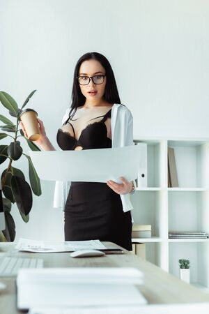 Selective focus of excited secretary in bra holding paper cup and papers in office