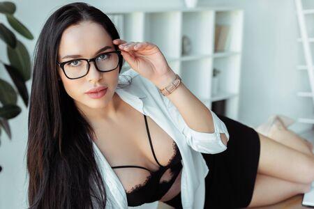Sensual secretary in bra holding eyeglasses while lying on table in office Standard-Bild