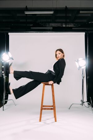 Side view of stylish model looking at camera while sitting on chair in photo studio