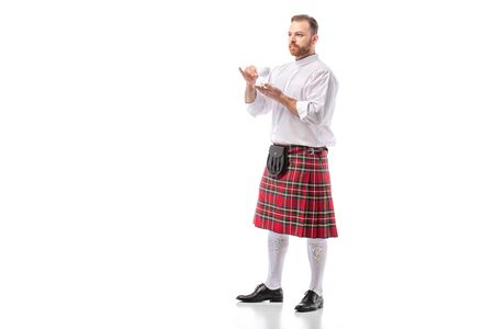 Scottish redhead man in red kilt drinking coffee on white background