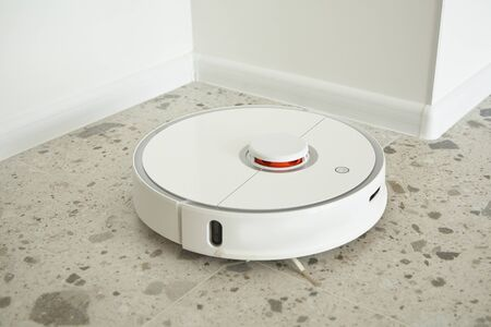 modern automatic vacuum cleaner washing floor tiles in apartment