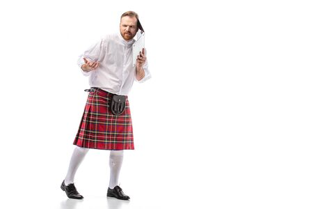 confused Scottish redhead man in red kilt holding laptop near ear on white background