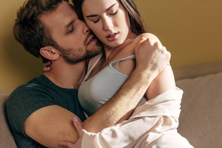 passionate man undressing and kissing sensual girlfriend