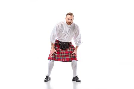 Scottish redhead man in red kilt in pose on white background