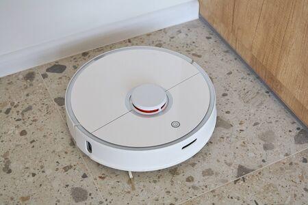 modern robotic vacuum cleaner washing floor tiles in apartment
