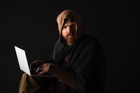 frowning medieval Scottish man in mantel using laptop in dark isolated on black Imagens