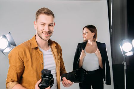 Selective focus of handsome photographer smiling while holding lens and digital camera near beautiful model in photo studio
