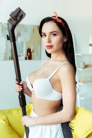 Side view of sexy girl looking at camera while holding brush of vacuum cleaner