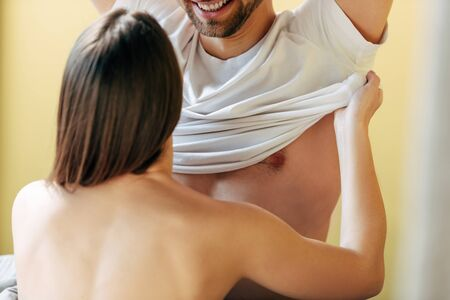 back view of young woman undressing cheerful man in bedroom Standard-Bild