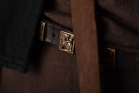 close up view of medieval Scottish brown clothing and belt with golden buckle