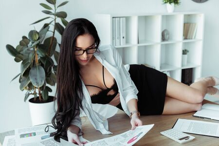 Beautiful secretary in bra working with papers while lying on table
