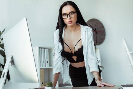 Sensual secretary in bra and shirt looking at camera near computer in office Standard-Bild