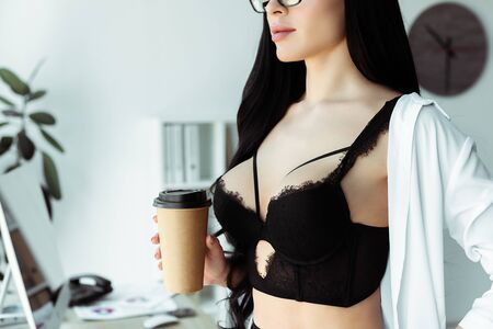 Cropped view of sexy secretary in bra holding disposable cup in office