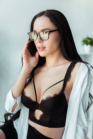 Sexy secretary in bra and shirt talking on smartphone in office