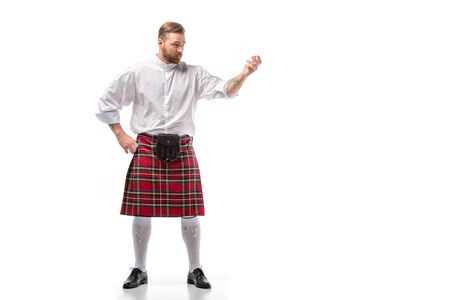 serious Scottish redhead man in red kilt on white background