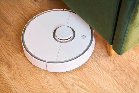 modern automatic vacuum cleaner washing floor near green sofa