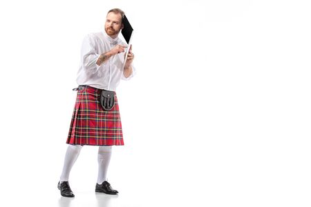 Scottish redhead man in red kilt holding laptop near ear on white background