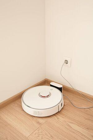 modern robotic vacuum cleaner near power socket on wall