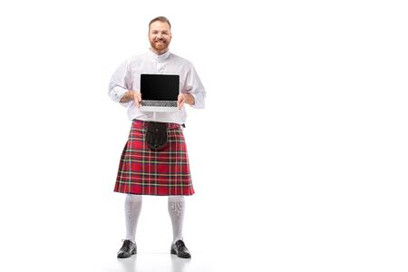 smiling Scottish redhead man in red kilt presenting laptop with blank screen on white background
