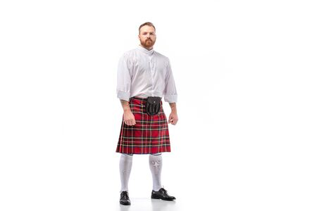 Scottish redhead bearded man in red tartan kilt on white background