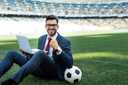 smiling young businessman in suit with laptop and soccer ball sitting on football pitch and showing yes gesture at stadium, sports betting concept