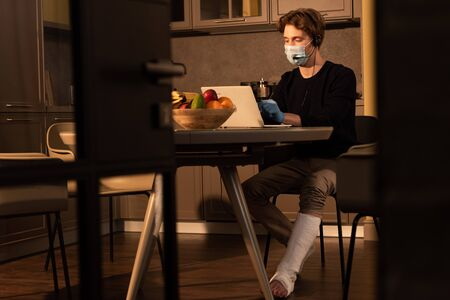 Selective focus of man in medical mask and plaster bandage on leg using headset and laptop in kitchen