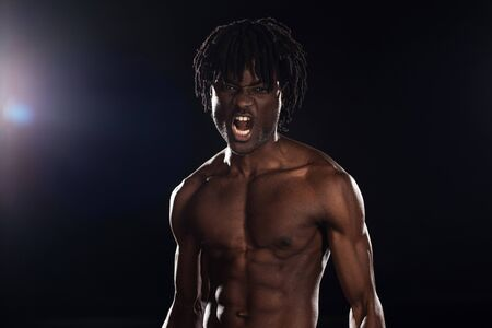 sexy aggressive african american man yelling on black with back light
