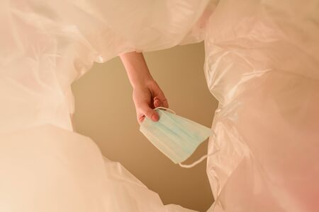cropped view of woman throwing medical mask in trash can, end of quarantine concept