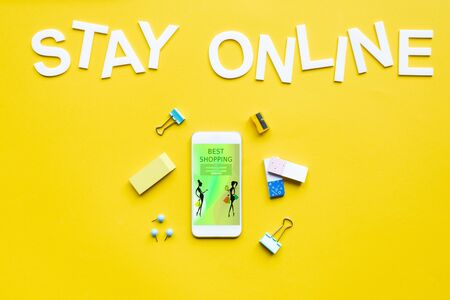 Top view of smartphone with best shopping app near office supplies and stay online lettering on yellow surface