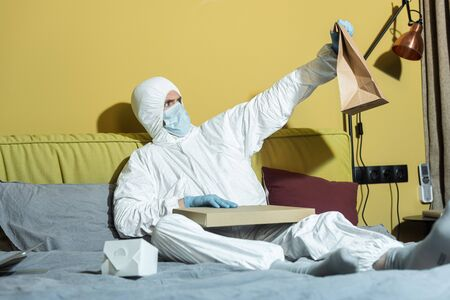 Selective focus of man in hazmat suit and medical mask holding package near pizza box on bed