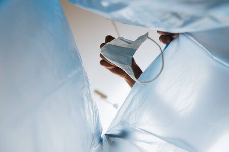 bottom view of man throwing medical mask in garbage bag, end of quarantine concept