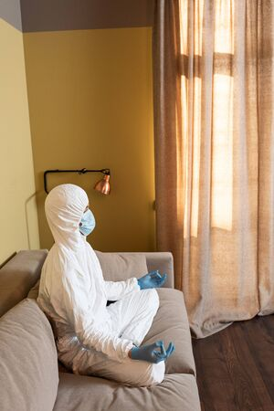 Side view of man in hazmat suit, latex gloves and medical mask meditating on couch Stock fotó