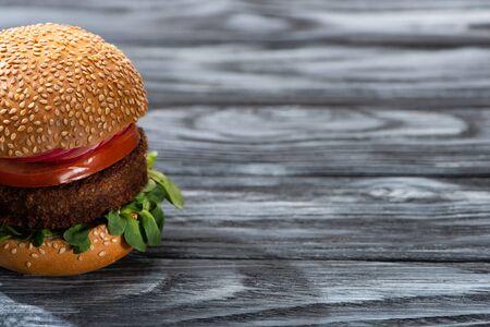tasty vegan burger with vegetables served on wooden table