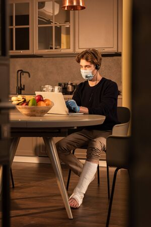 Selective focus of disabled man in medical mask using headset and laptop near fruits on kitchen table