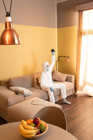 KYIV, UKRAINE - APRIL 24, 2020: Selective focus of man in hazmat suit and medical mask holding joystick on sofa at home